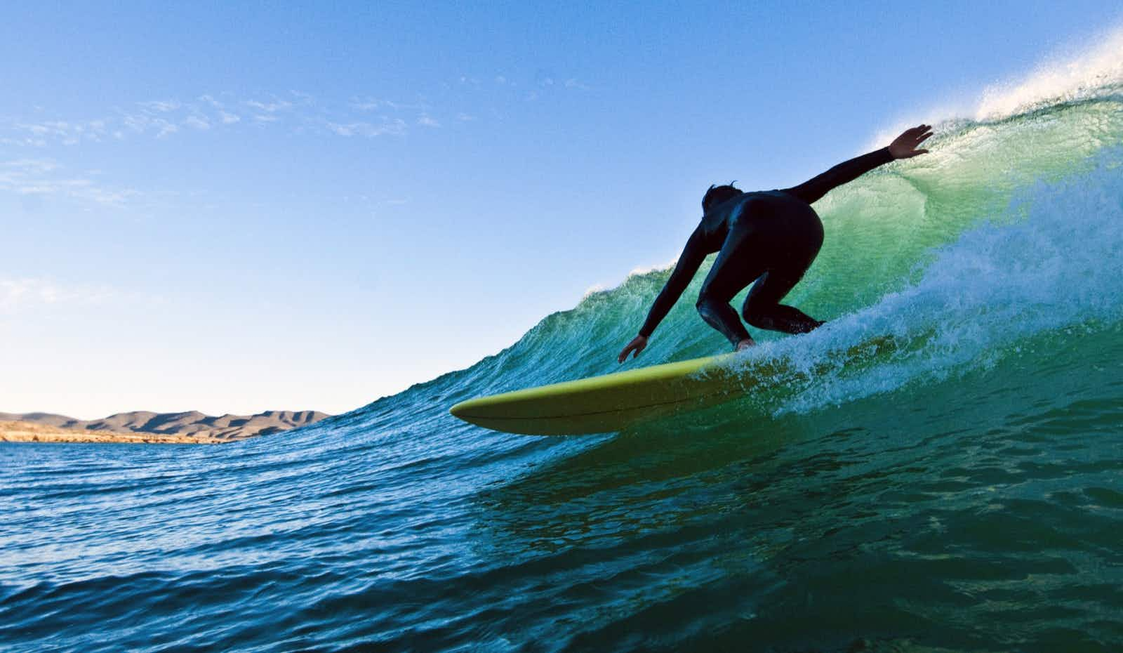 A surfer in a black wetsuit slides down a green wave with the sun behind it in Mexico