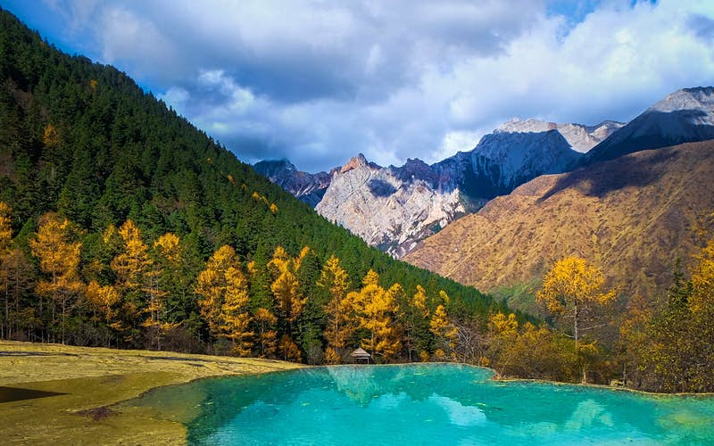 An emerald lake and mountains in autumn.