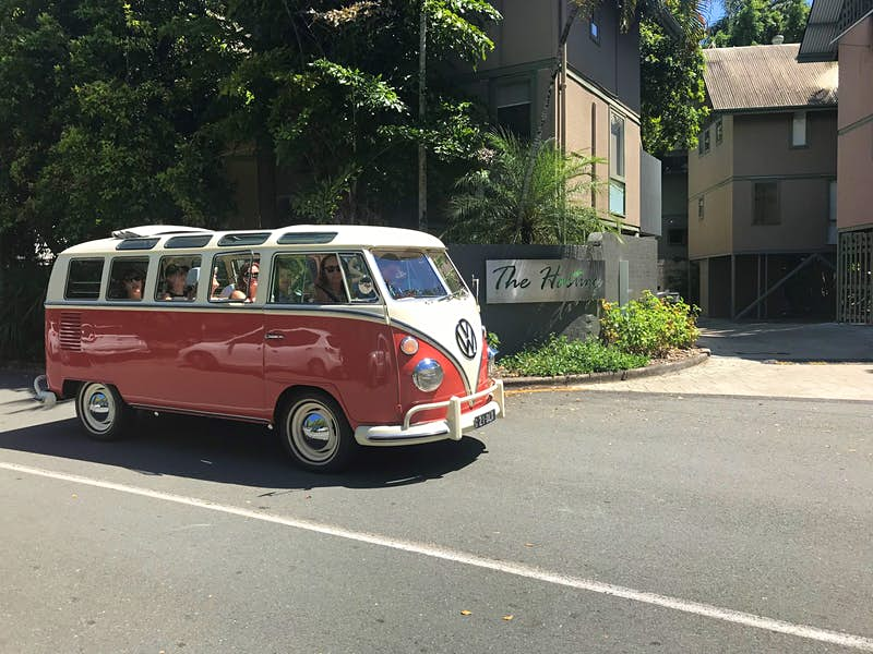 A retro VW Kombi van, with bright red bottom and white top (which converge to a point at the front bumber), drives along a tree-lined street in Noosa; there are numerous individual windows along the van's side and on the edge of the roof, and the middle of the roof is retractable, with the fabric piled near the rear