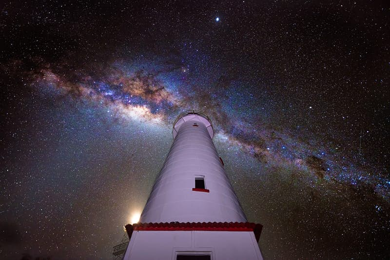 A purplish glow lights the exterior of the white Lady Elliot Island lighthouse, which rises and narrows as it climbs skyward to the heavens above; the black sky is cut from left to right by blue, gold and purple hues of the Milky Way