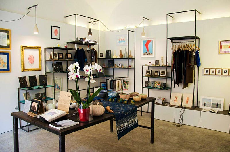 The interior of Materia Mediterranea's shop, with clothing on a rail and art and ceramics on tables and shelves