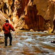 A man hiking through a river into the narrows in Zion National Park, Utah USA.