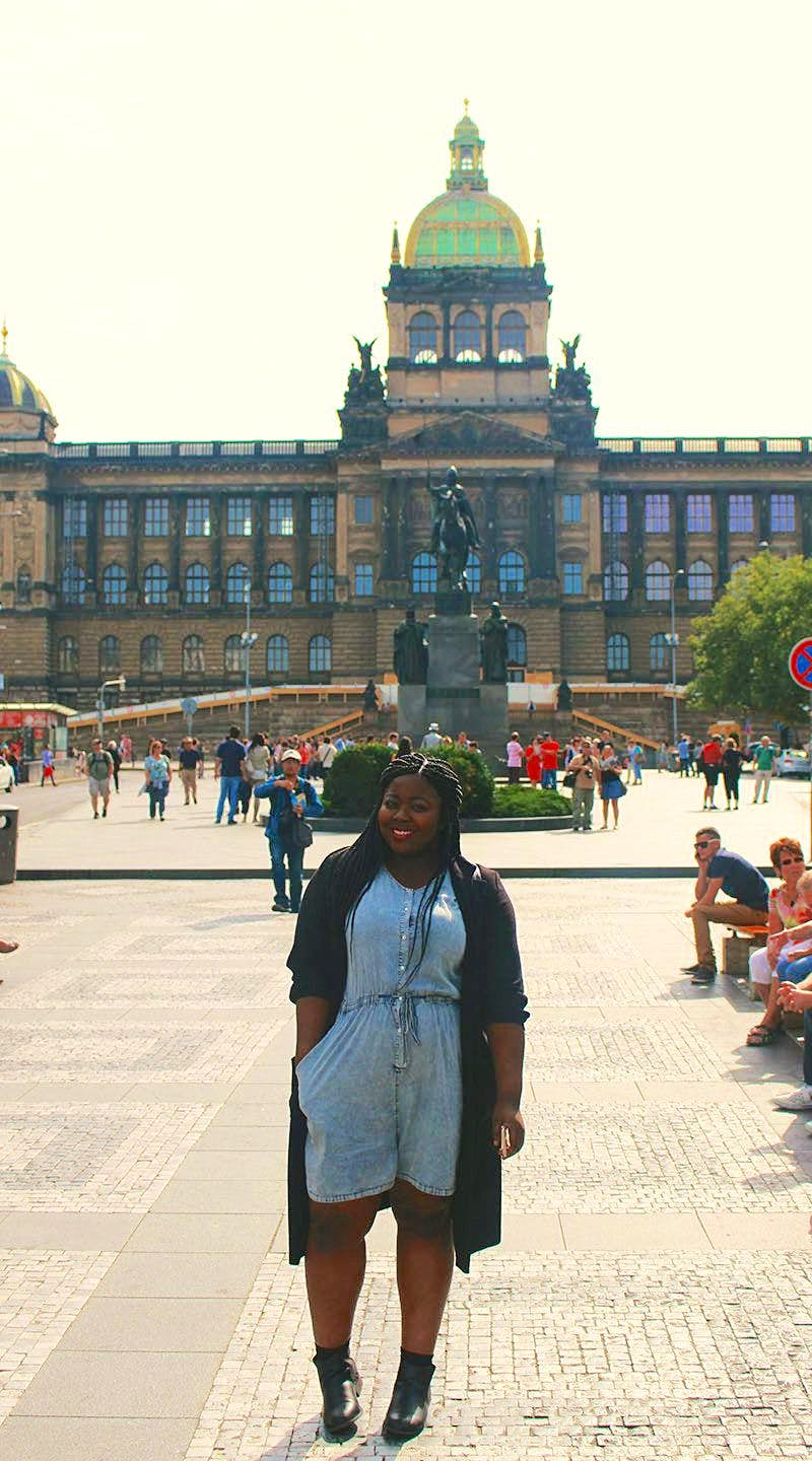A young black woman smiles for the camera in the sun-dappled square in front of the National Museum in Prague. Black girl travelling tip for Prague, be prepared to see swastikas.