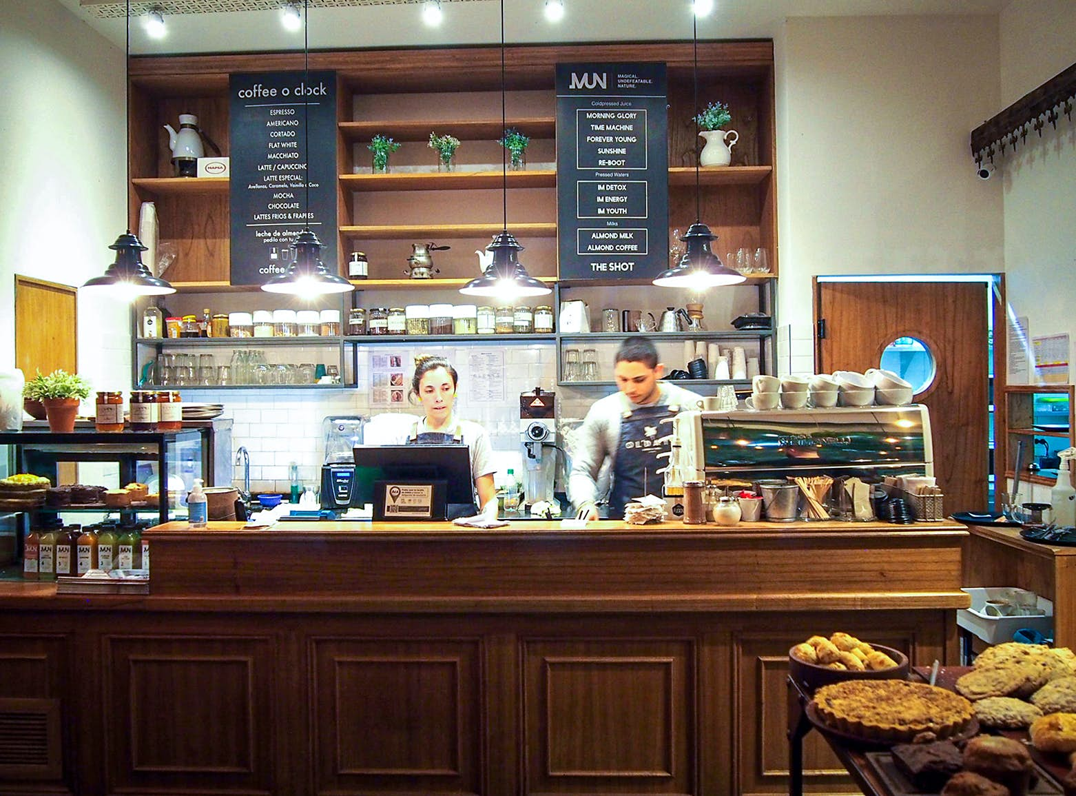 Two people work behind a wooden counter with pies and beverages displayed around them