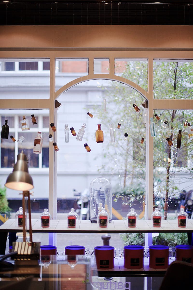 Dublin independent shops - Parfumarija's window display with brown bottles of different sizes dangling at a variety of heights in a lovely arched window with white frames. There is a shelf of bottles neatly arranged in the foreground