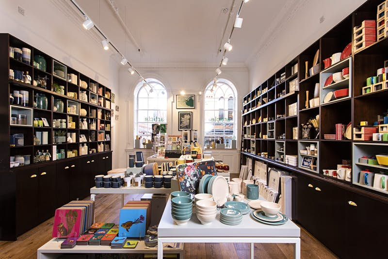 Dublin independent shops - the interior of Article. Tall dark shelves line the white walls stocked with colourful bowls, cups, jugs and homewares. In the foreground there is a white table with notebooks and more bowls. There are large arched windows on the back wall