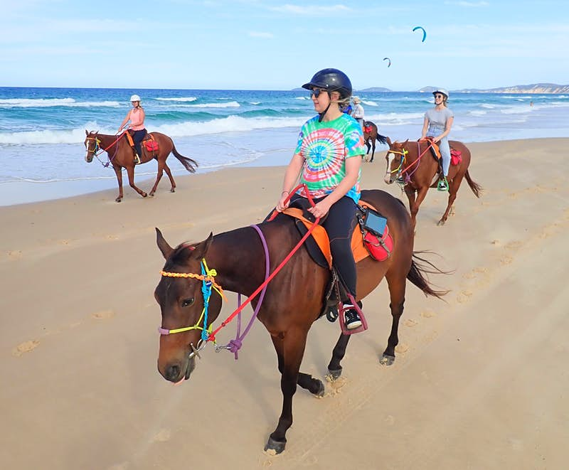 A young woman wearing a tie-died t-shirt, black grousers, helmet and sunglasses rides a chesnut-coloured horse with brighly coloured reigns, which range from purple and orange to red, blue and green; behind her are two other riders on the same section of beach, with crashing waves beyond and two kite-surfers in the distance