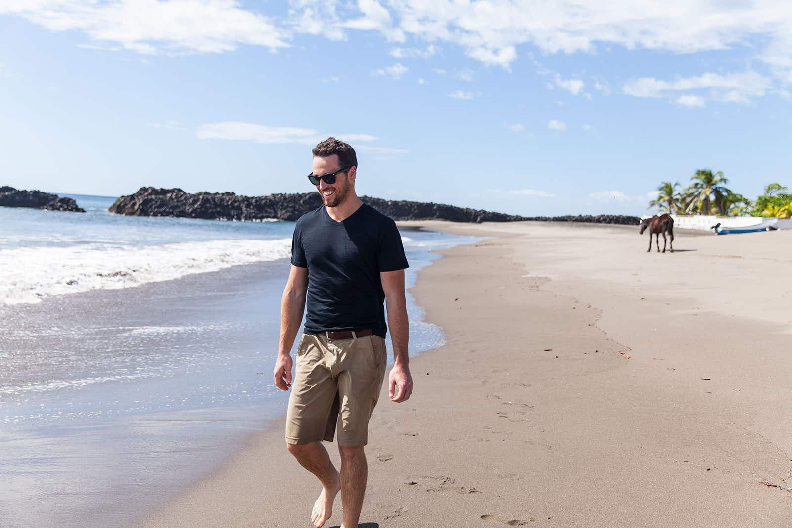 Man walking along a beach while wearing an Unbound Merino shirt; great travel gifts for father's day