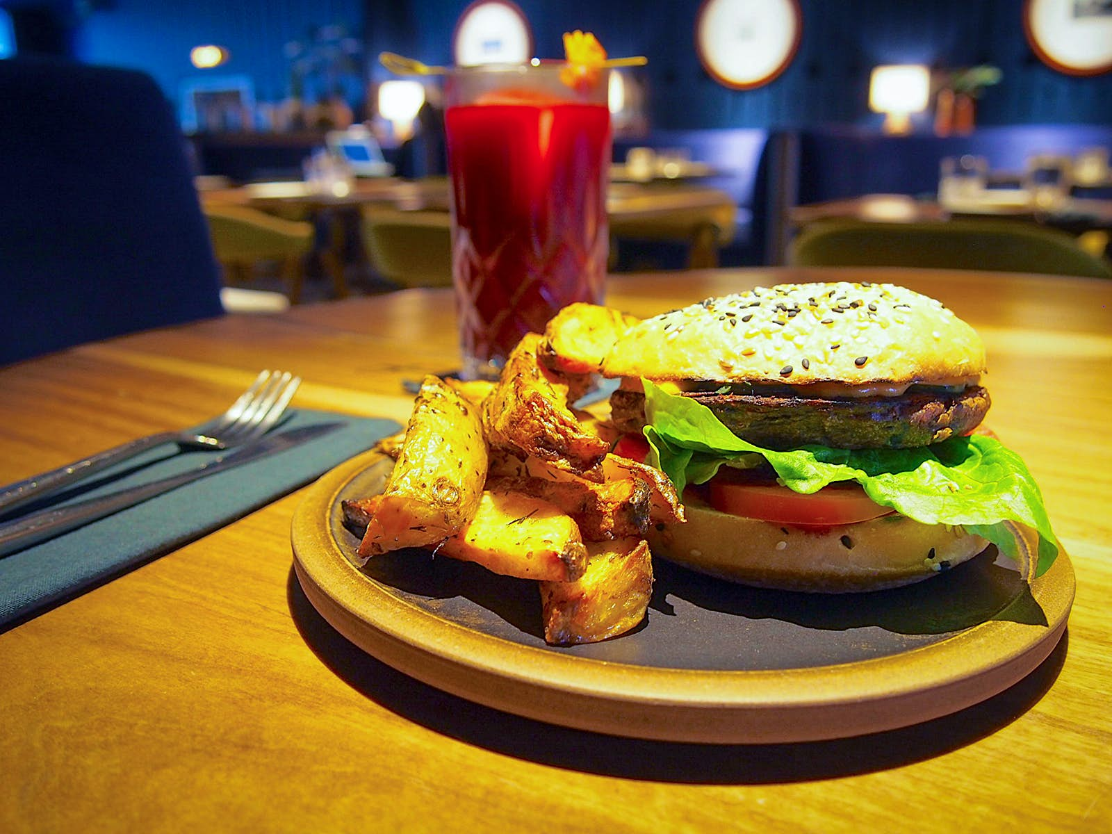 A delicious-looking veggie hamburger is surrounded by thick cut potatoes. The burger has lettuce and tomato on it