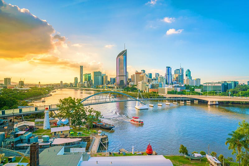 Looking down over the Brisbane River, with the city skyline of large glass towers in the background; the sky ranges from deep blue on the right to burning yellowy orange on the left, with the sun behind a bank of cloud; a small ferry makes its way under a bridge and towards the camera