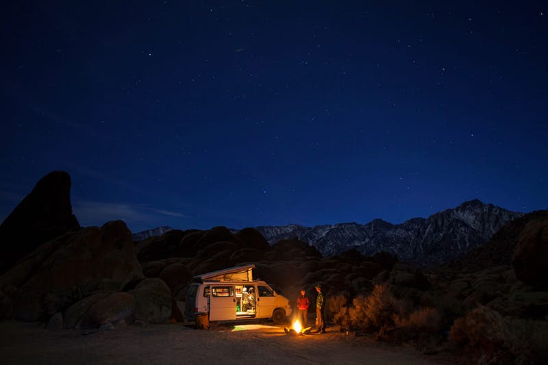 Two people stand by a campfire in front of their motorhome on a camping trip.