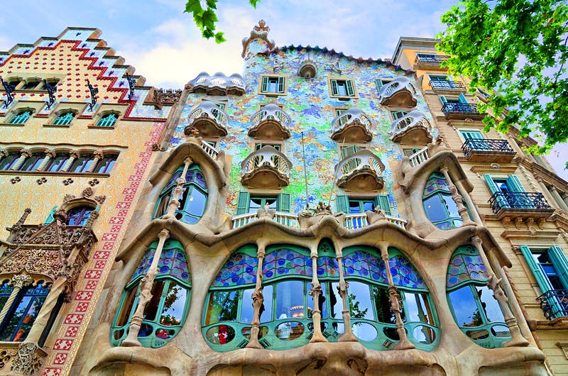 A low-level view of the whimsical facade of Casa Batlló in Barcelona; it is sprinkled with bits of blue, mauve and green tiles and studded with wave-shaped window frames and balconies, rising to an uneven roof with a solitary tower.