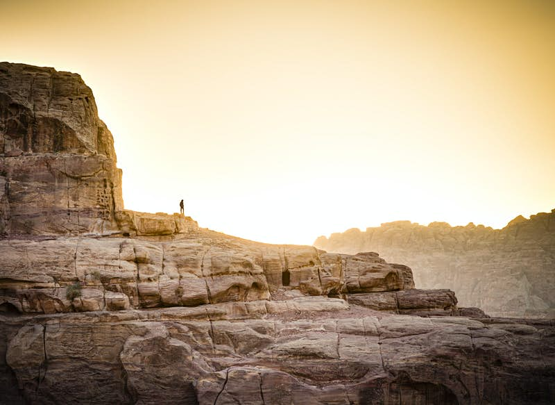 Lone hiker standing on the rock in Petra, Jordan at sunset