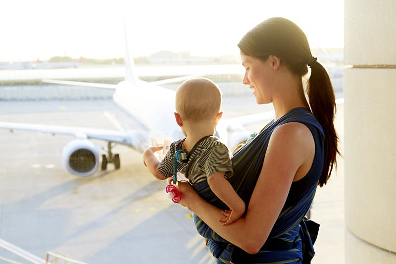 A mum looks lovingly down towards her young baby in a sling on her chest. The baby is looking away from the camera and out a window in the airport to a jet on the tarmac