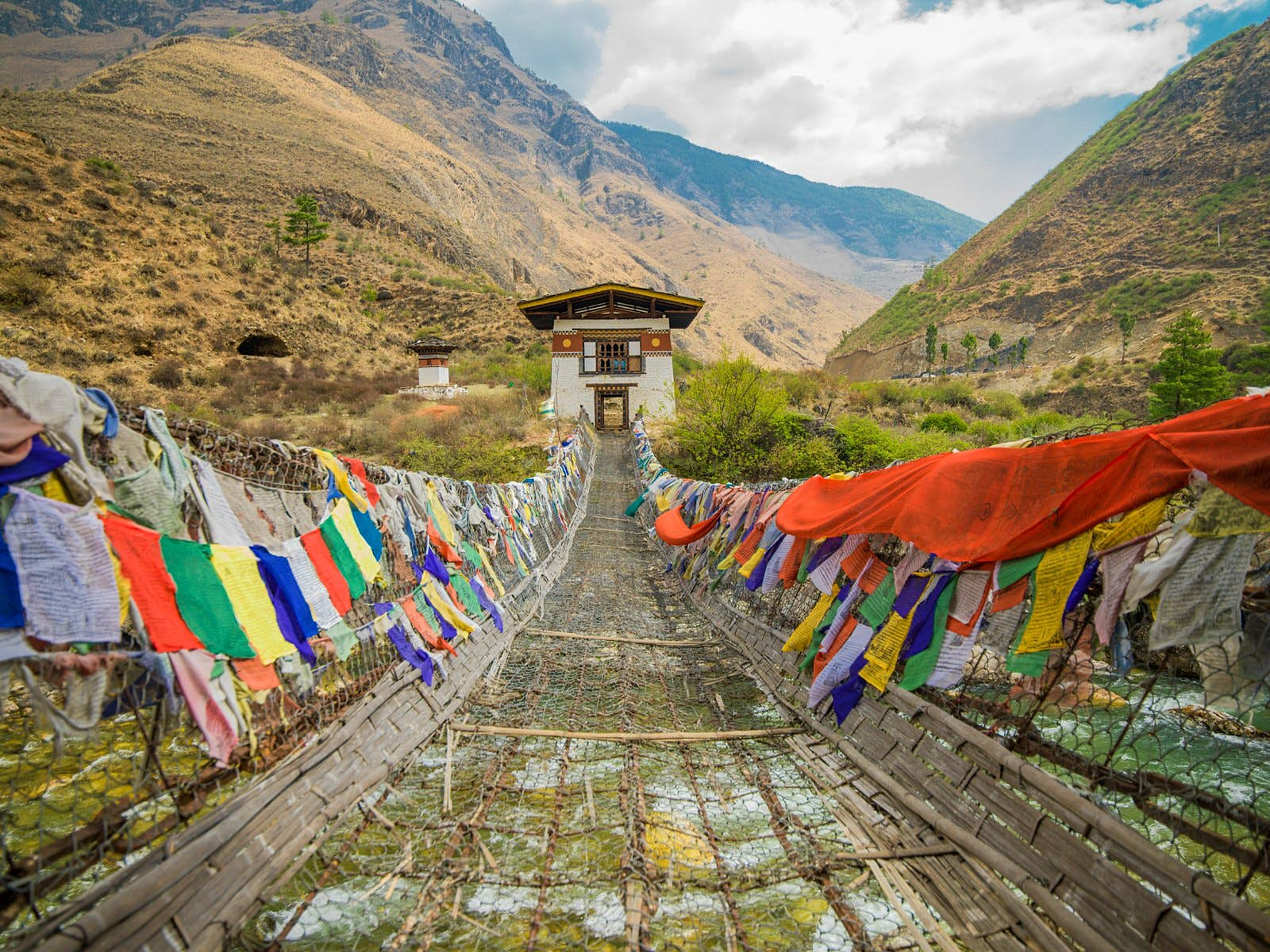 Tachog Lhakhang Iron Chain Bridge with colourful prayer flags on each side of bridge