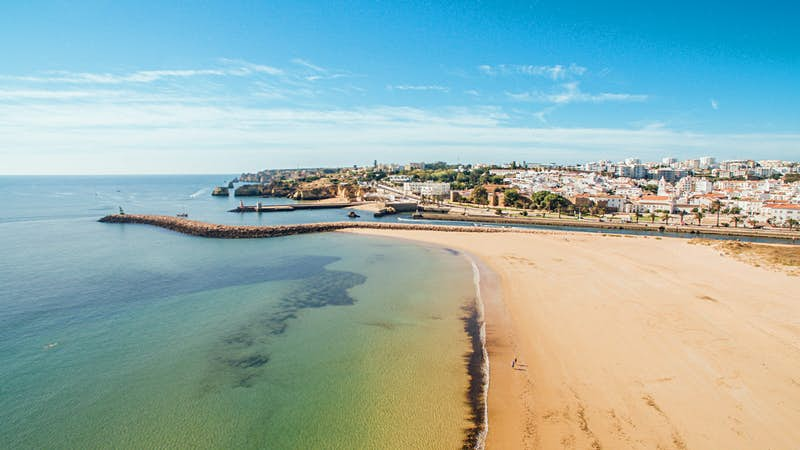 An aerial view of beautiful Meia Praia beach in the Algarve town of Lagos in the morning: a harbour wall and a river separate a huge deserted expanse of sand from the white buildings and ochre roofs of the town beyond, while a bright blue sky shines down on crystal-clear waters.