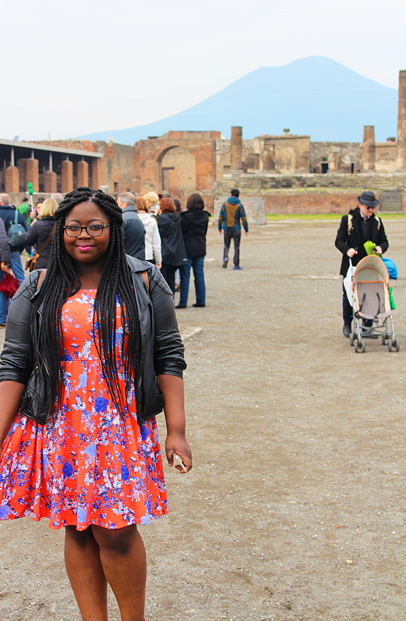 A young black woman poses in the foreground and some ruins in Pompeii are visible in the background. Other visitors mingle around; she is standing alone. Mount Vesuvius looms in the background of the photo. A black girl travelling through parts of Italy may experience racism.