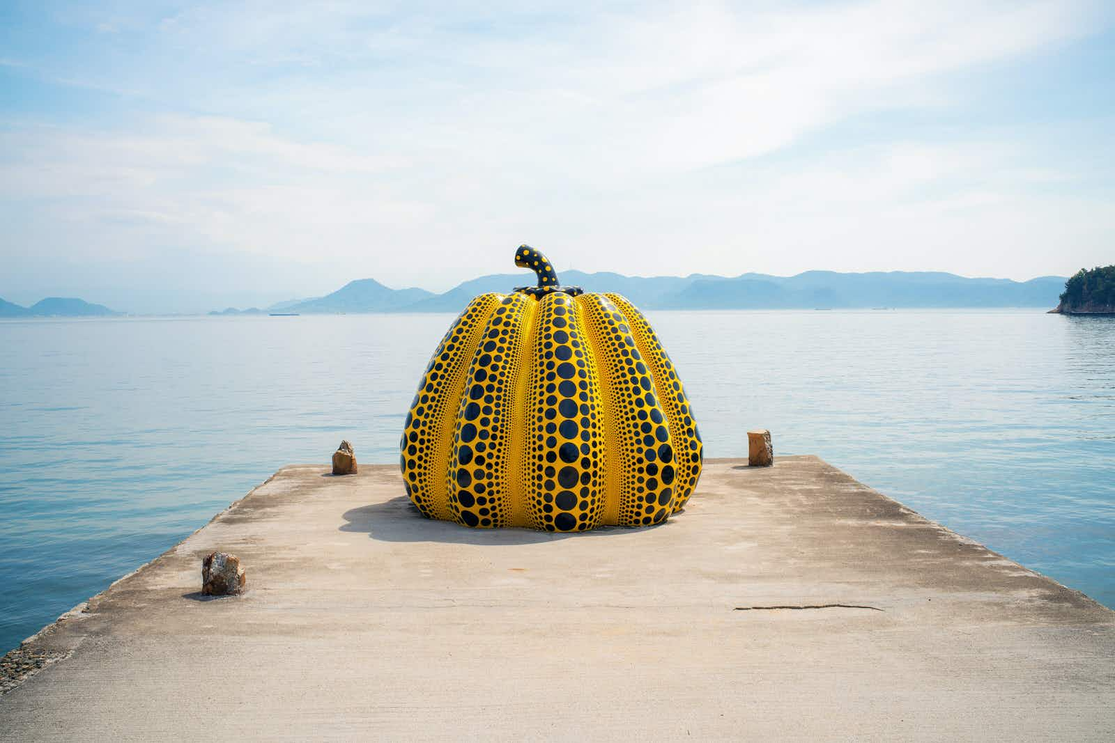 A giant yellow and black pumpkin sculpture at the end of a concrete jetty in front of the sea in Naoshima, with hilly islands visible in the background