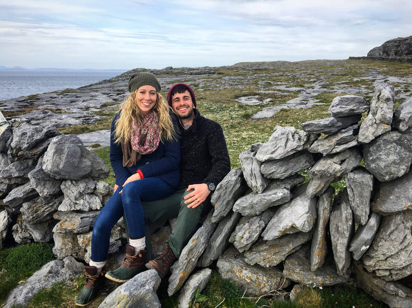 A young couple sit on a traditional stone wall in the Irish countryside, they are both wearing hats, boots, jeans and sweaters and the woman is wearing a scarf.