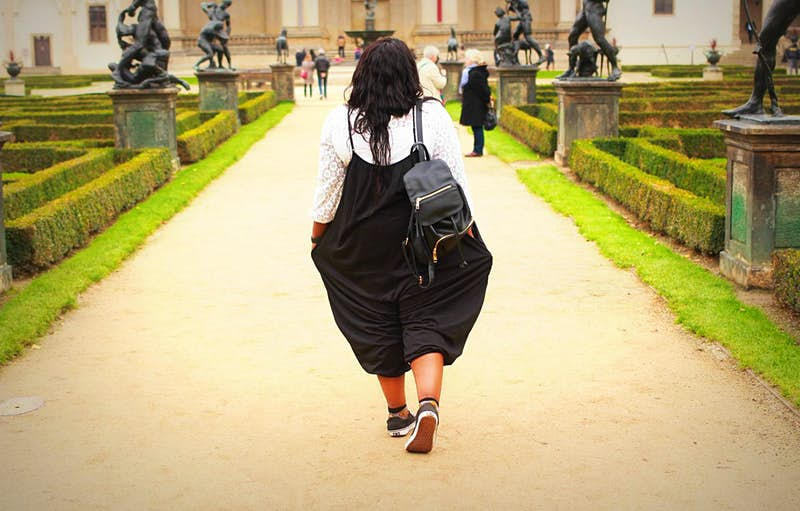 A black girl travelling through Prague. She's wearing a backpack walks along a path in a public garden in Prague. She is facing away from the camera.