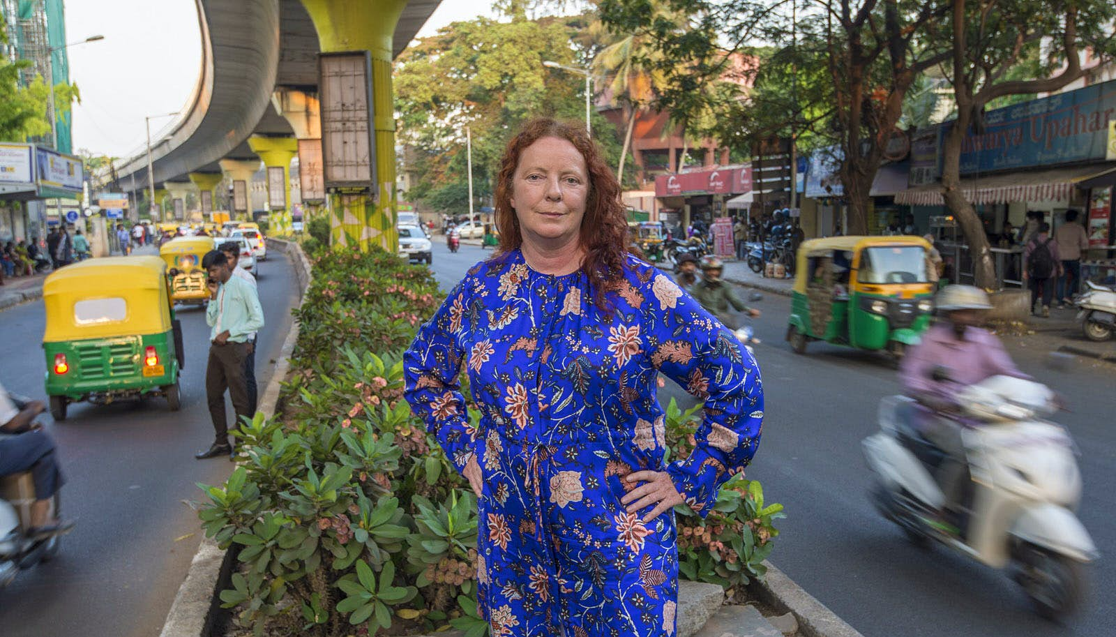 The author poses in India. She is standing in an island in the middle of a road, wearing a blue dress. Tuk tuks, mopeds and cars are speeding past her on either side.