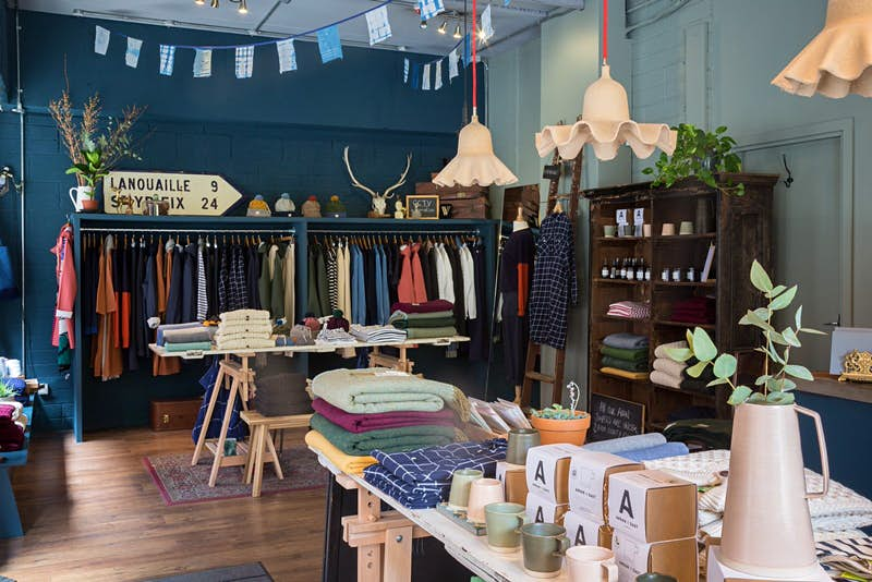 Dublin independent shops - the interior of Scout. There is a rail of multicoloured clothes against a teal wall with a road sign and horned skull on top. Blue bunting hangs from the roof and there is a table of folded clothes, mugs and homewares in the foreground as well as a variety of lampshades hanging at different lengths from the roof