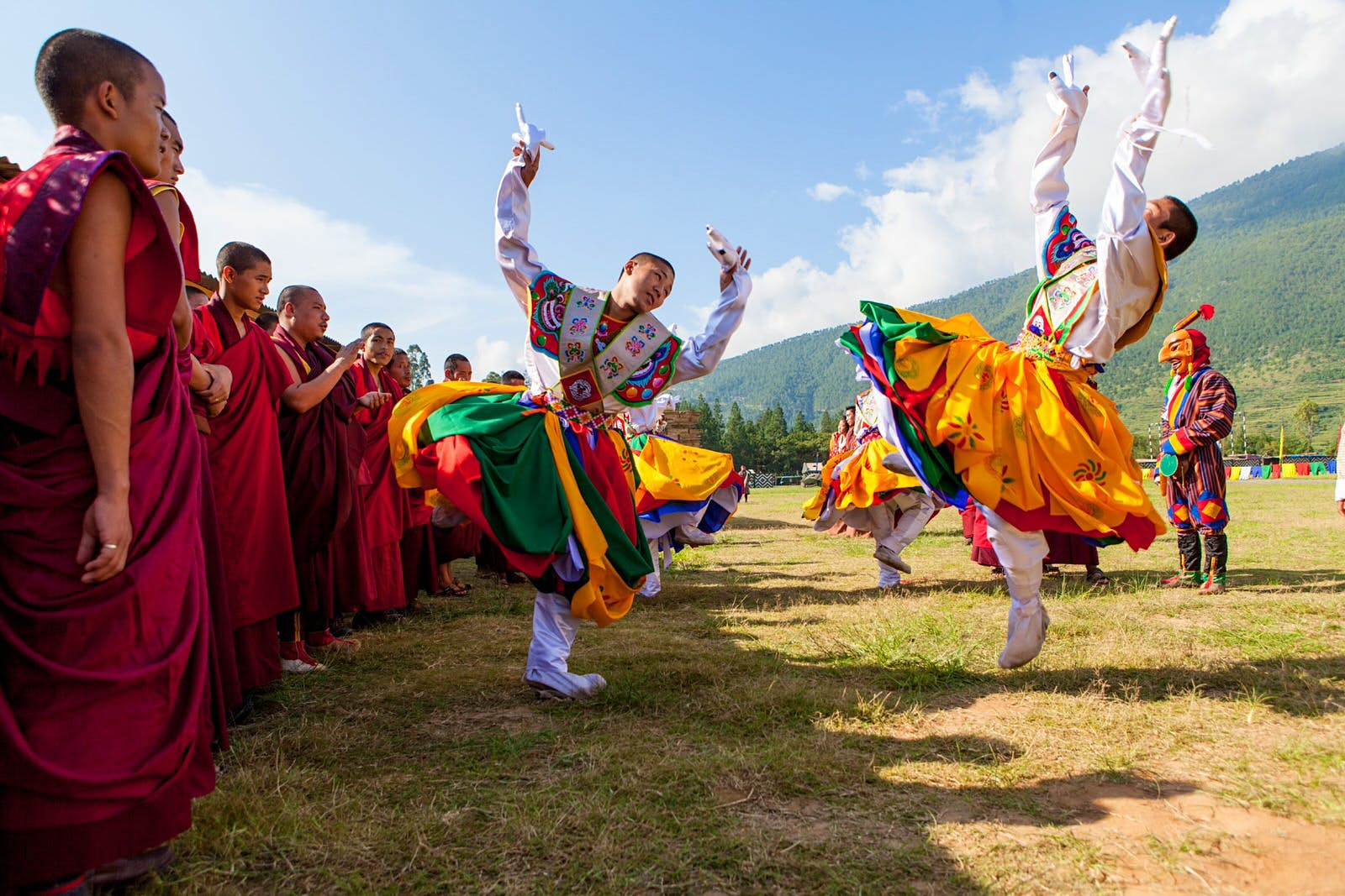 Monks in red robes line up on the left side watching men in colourful suits leap in the air as part of the dance.
