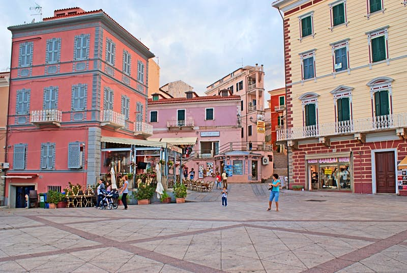 Pastel buildings surrounding a plaza; best things to do in Sardinia