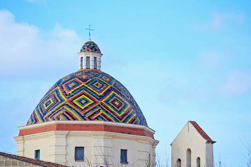 A colorful dome roof of mosaic tiles under a blue sky; best things to do in Sardinia