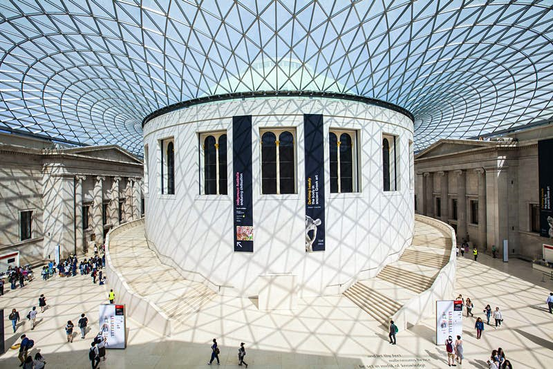 The central hall of the British Museum is a large round white space flooded with light from the glass ceiling