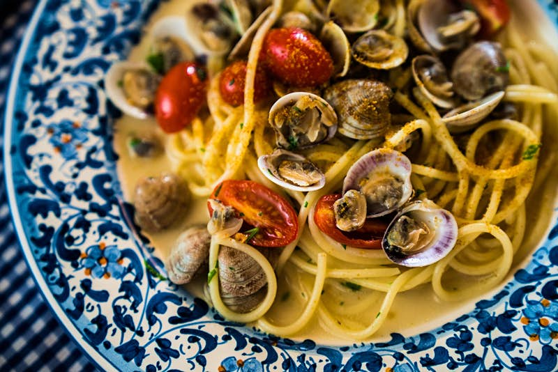 A blue-and-white plate filled with spaghetti noodles, clams and red tomoatoes; best things to do in Sardinia