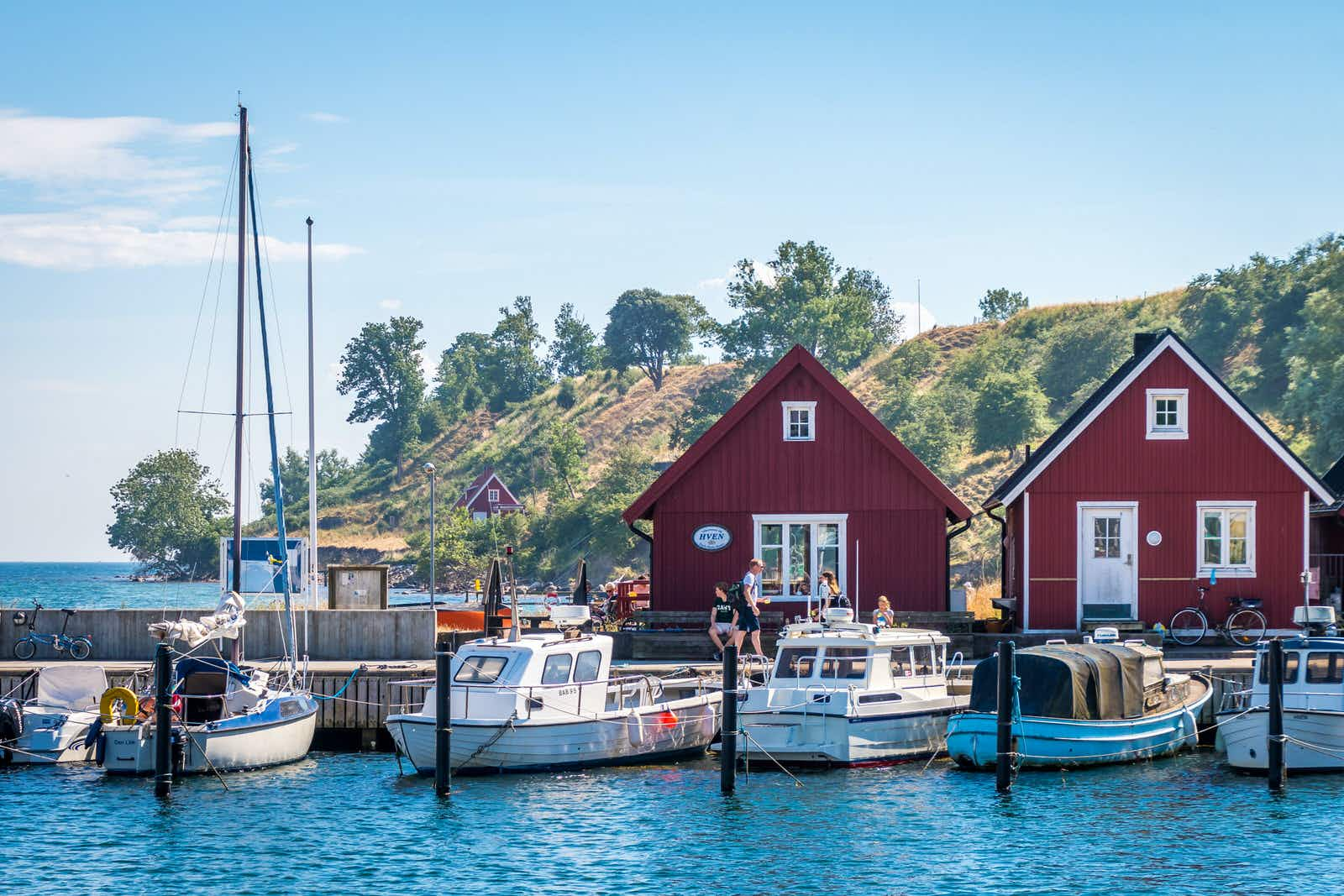 Small boats are docked in front of two red triangular buildings on a sunny day on Ven island, Sweden