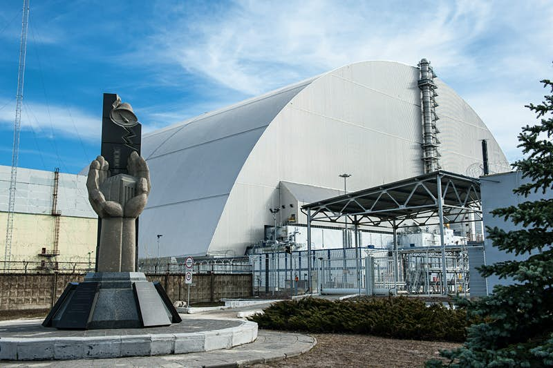 In the foreground is a concrete memorial to the Chernobyl disaster, depicting two hands cupped together around a miniature of Reactor 4; behind the memorial is the huge grey arch of the New Safe Confinement structure that encloses the remains of Reactor 4.