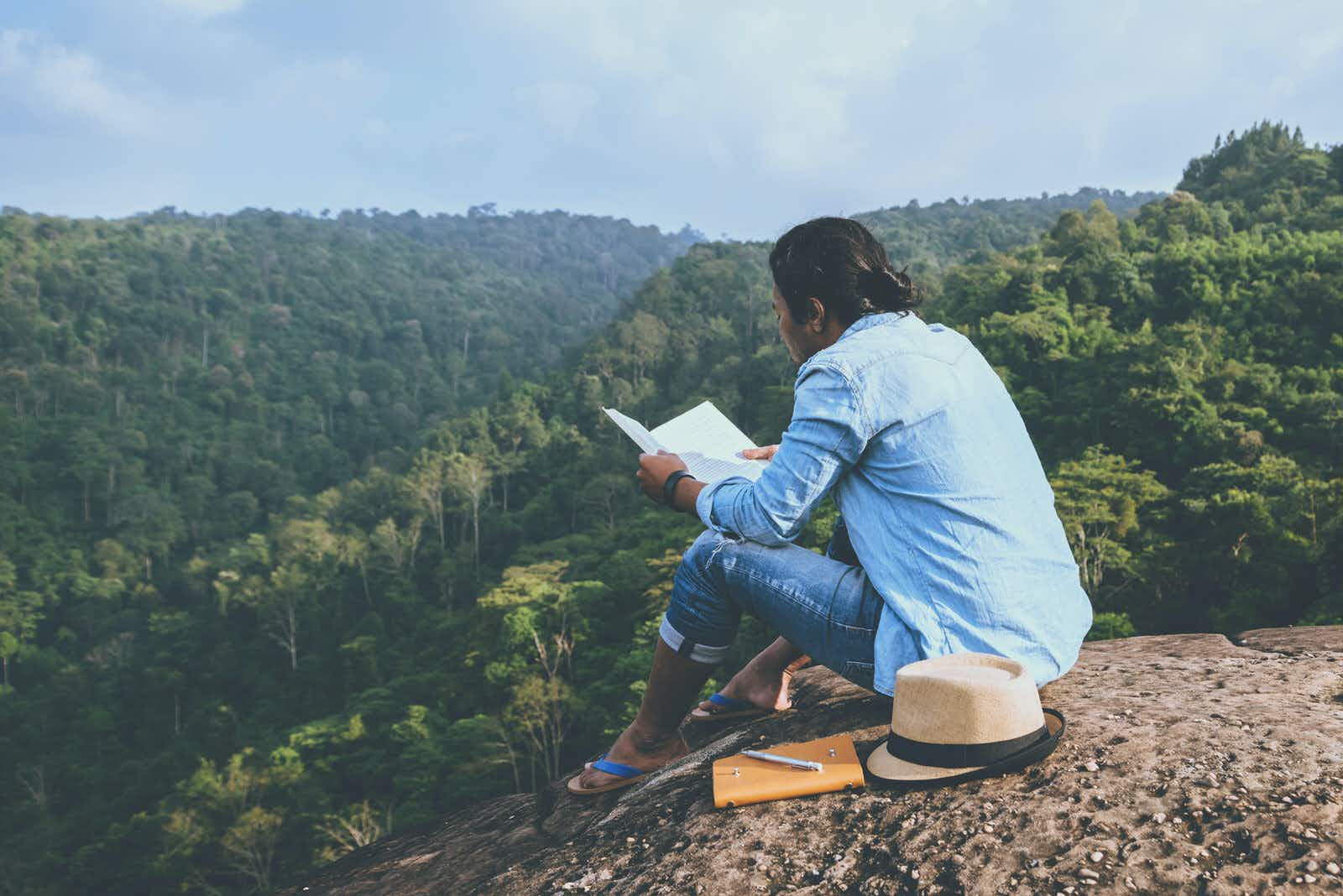 A person sitting on a rock reading a book next to a notepad, pen and hat. The person is wearing a denim shirt, jeans and flip flops and beyond the rock there is a view of rolling greenery