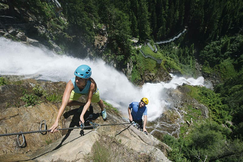 Two climbers hold a metal rope, as the Stuibenfall waterfall gushes behind them