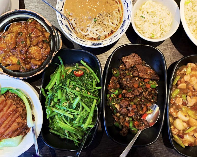 A selection of Sichuan and Hunan dishes at Yipin restaurant. The close-up shot shows a chicken dish, a beef dish, green vegetables and chillies, rice, noodles and seafood in black and white bowls.