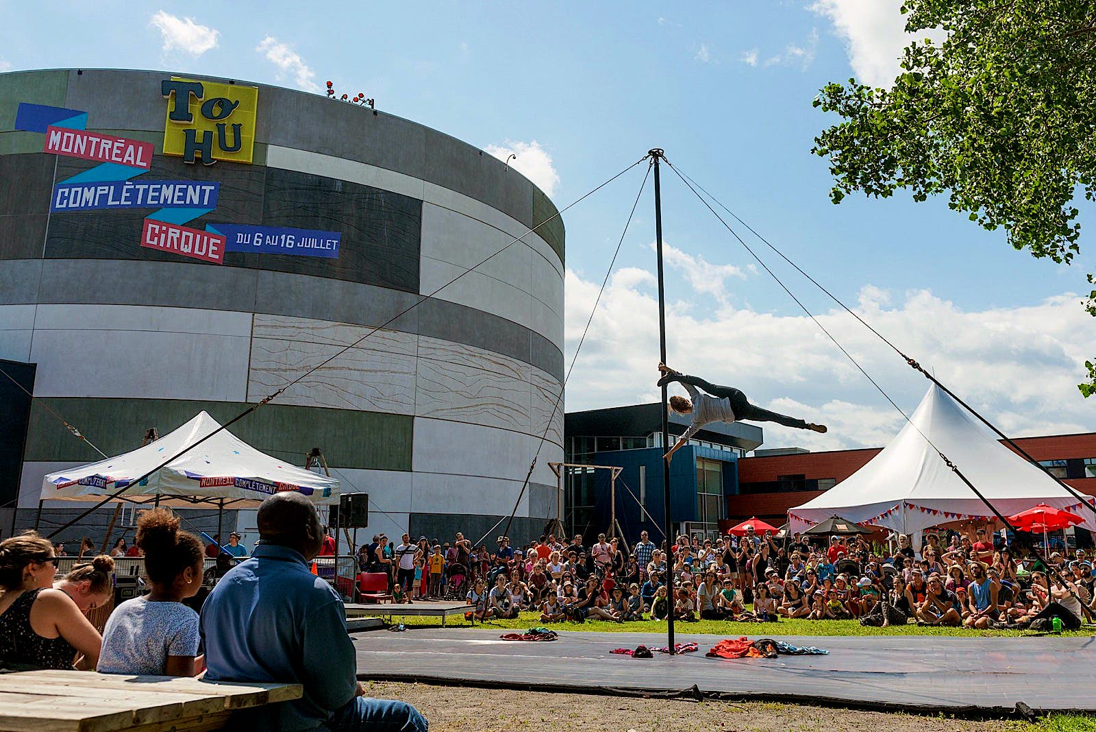 A circus acrobat performs on a vertical pole surrounded by tents and crowds, in front of the circular TOHU building in Montreal