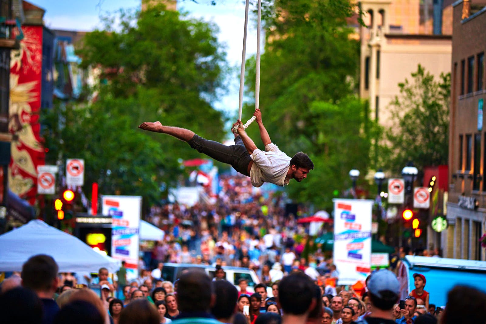 A circus acrobat is suspended above a crowd of spectators in the streets of Montreal