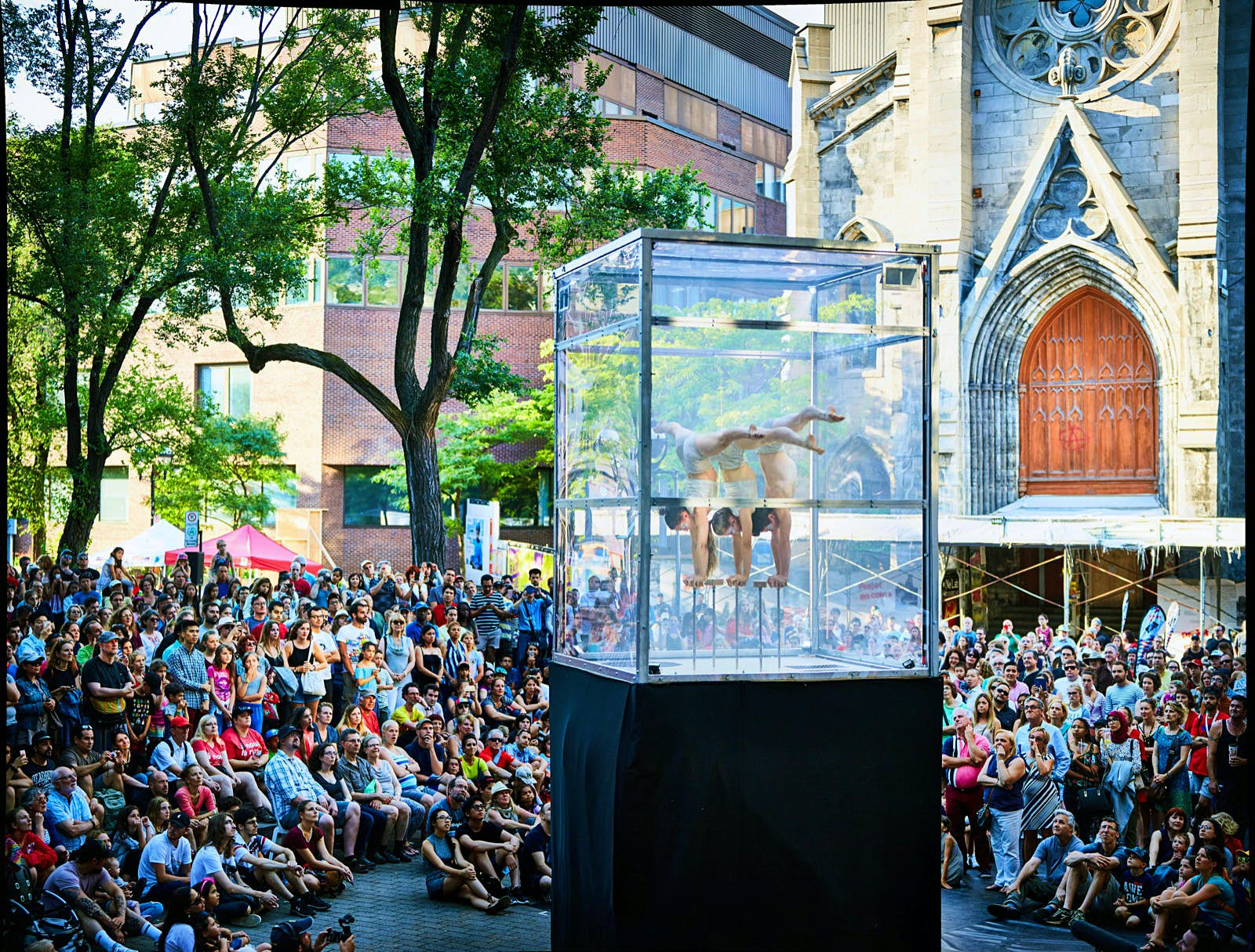 Three circus acrobat/contortionists balance on their hands on small stands inside a clear box on a pedestal, surrounded by spectators in Montreal
