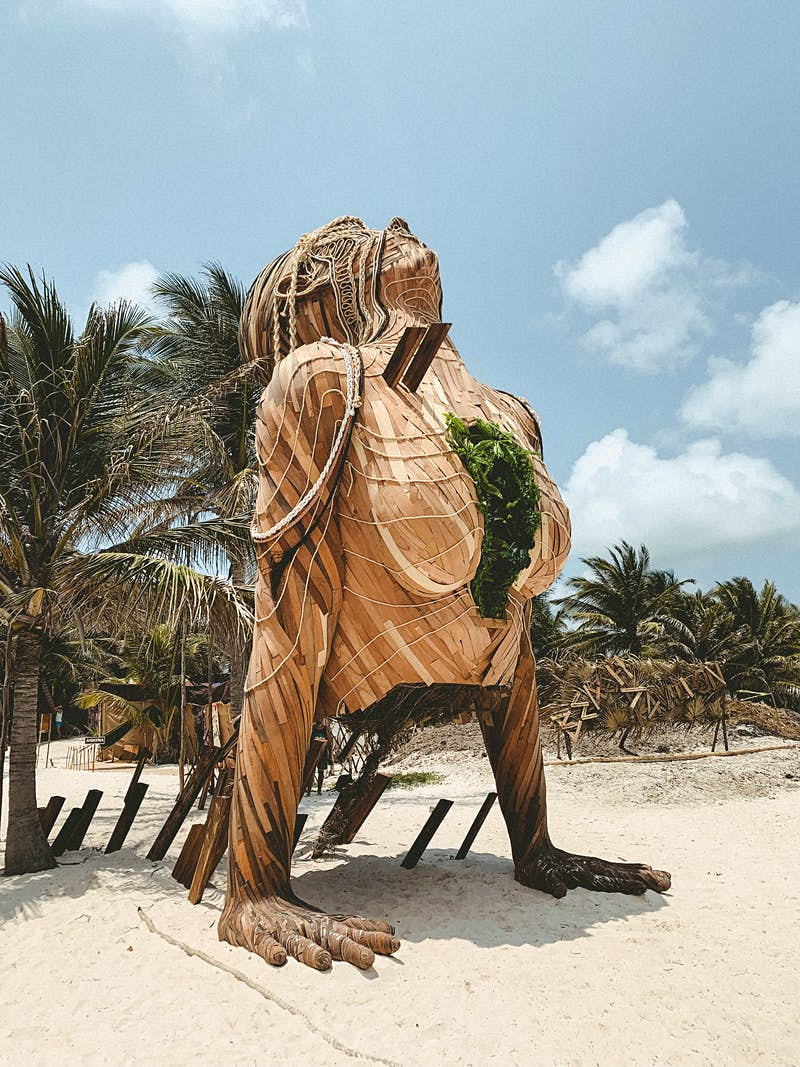 A huge wooden statue on a sunny beach of a woman's torso with hands splayed out on the sand, and face upturned to the sky; it wears a necklace of green leaves, and there are palm trees behind.