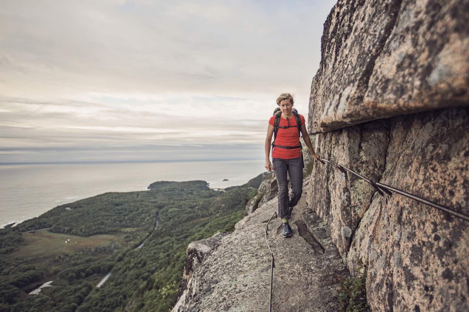 A woman hikes along the cliff edge in Maine's Acadia National Park, Maine