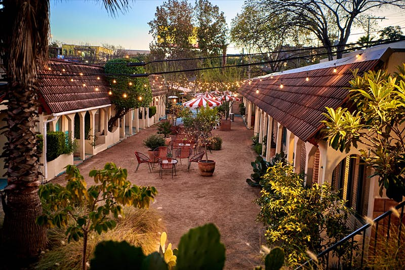 A motel courtyard with string lights, plants and seating