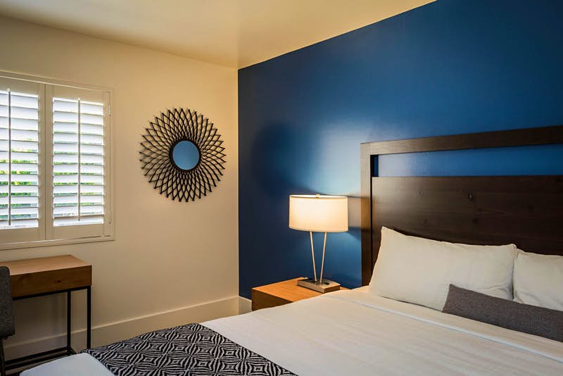 Interior of a room at Beck's, with a blue accent wall and modern furniture; coolest motels