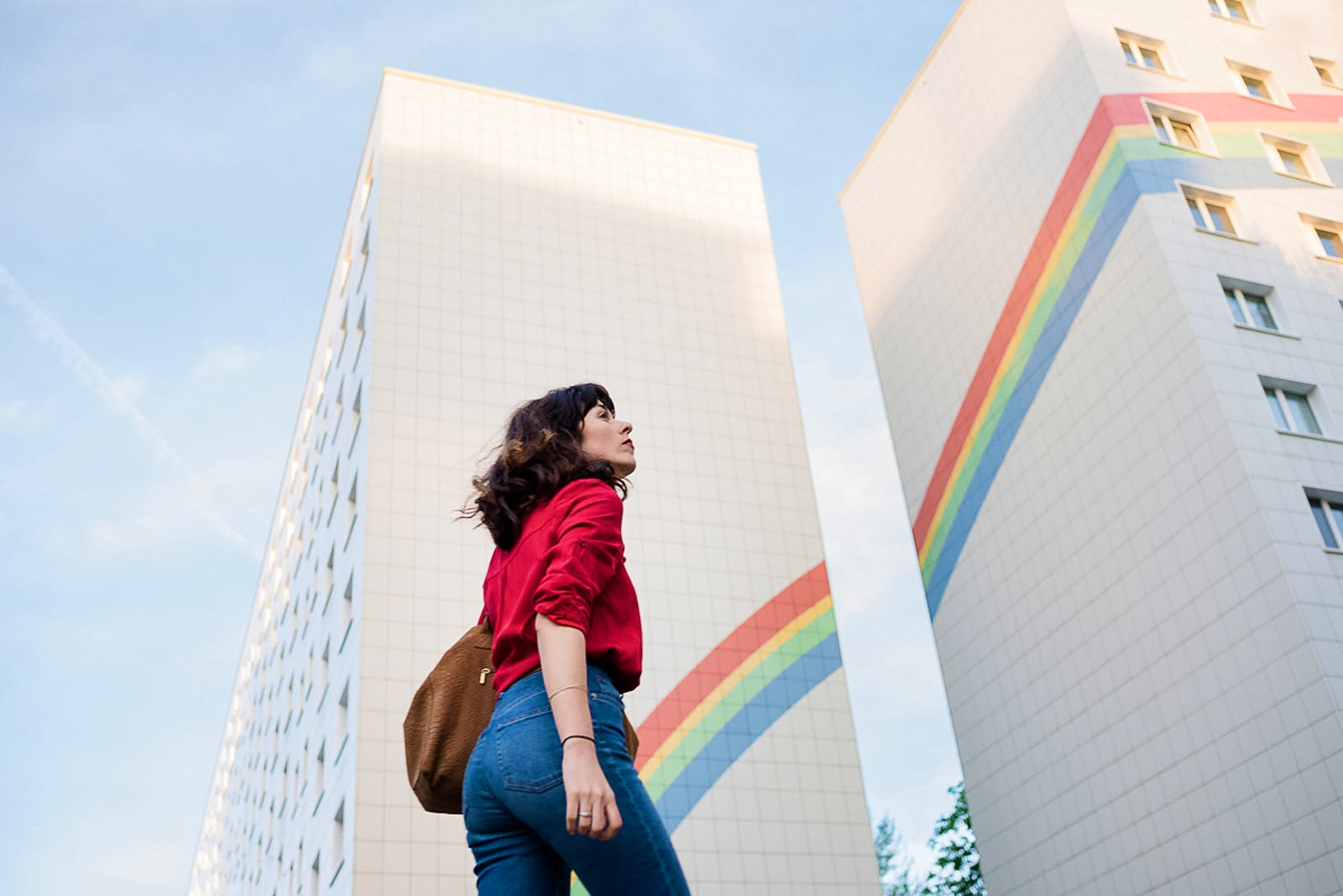 A woman looks to the sky against the the backdrop of a building in Berlin with a rainbow painted across it.