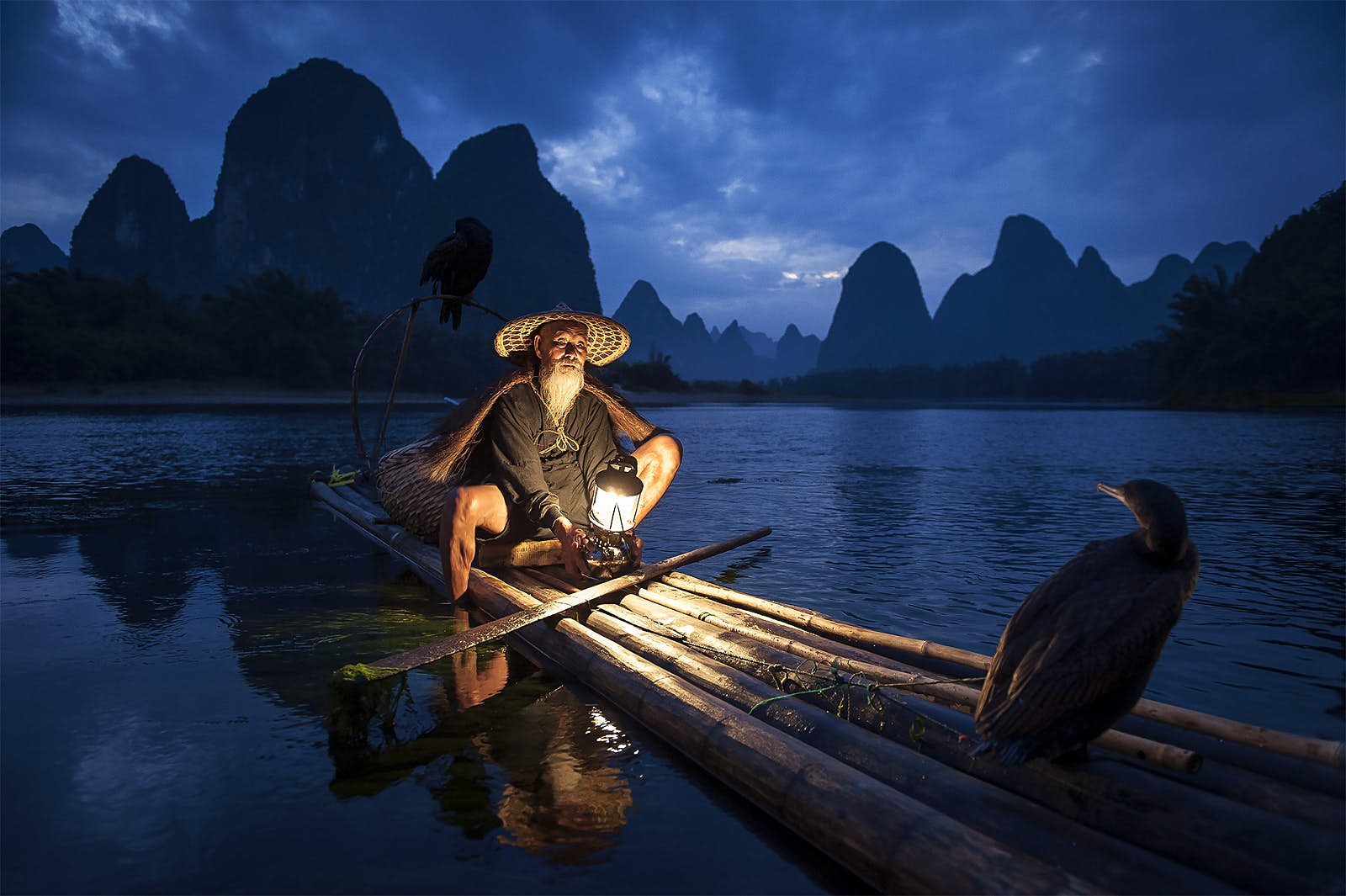 A boatman in Guilin, China; he sits in his long traditional boat made from tree branches at night, with a lantern illuminating him; he wears a wide-brimmed hat. There is a bird of prey sat at oneend of the vessel while in the background are a stretch of water and dramatic karst mountains.
