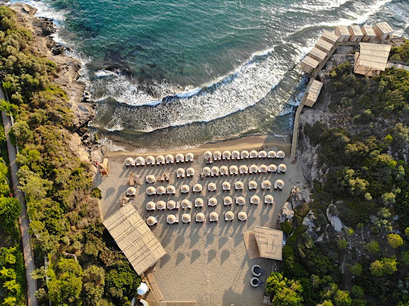 Birds'-eye view of a small beach covered with umbrellas; all-inclusive resort adventures
