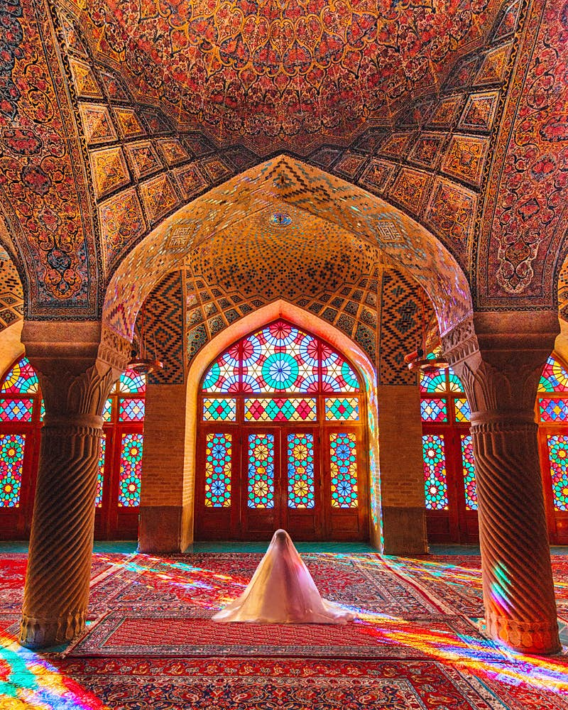 Symmetry looks great on Instagram; inside the colourful Nasir-ol-molk Mosque in Iran; there is an intricately patterned red carpet, and columns support a vaulted ceiling adorned with astonishingly detailed tilework. In the centre someone is praying covered in a white veil.