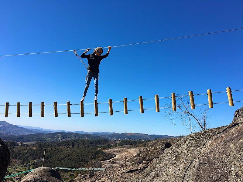 A woman traverses a rope suspension bridge amid rocky hillside scenery.