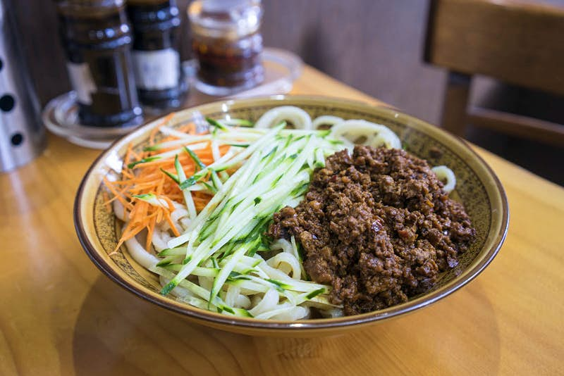 A close up shot of a bowl of zha jiang mian, served at EJ Fine Food restaurant in Melbourne. The dish has fresh shredded vegetables, beef and noodles.