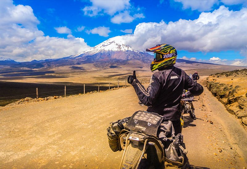 a person gives a thumbs up while on a motorcycle with a towering snow capped peak in the back ground on an epic adventure